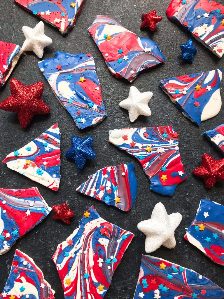Red, White, and Blue Patriotic Bark is a simple and easy dessert great for holidays like Memorial Day, 4th of July, and Labor Day. Candy melts and sprinkles are swirled for a festive kid friendly sweet. #patrioticdessert #redwhitebluedessert